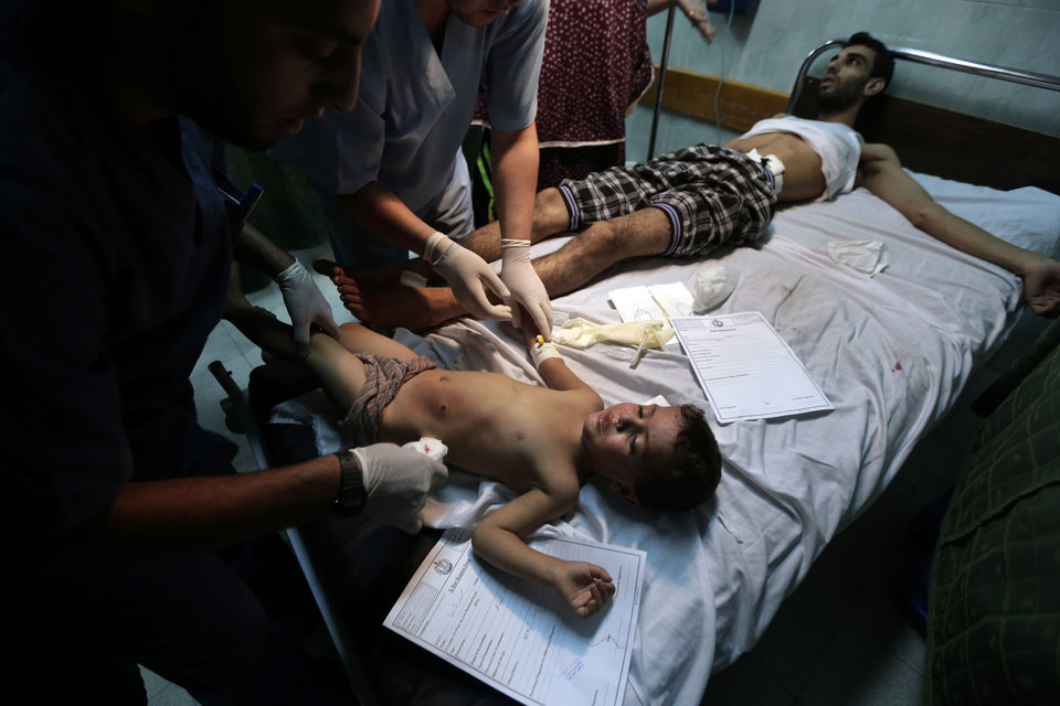 Photo - A Palestinian boy who was wounded in an Israeli strike on a house in Beit Lahiya shares a bed with an adult as they are treated at the emergency room of the Kamal Adwan Hospital, in Beit Lahiya, northern Gaza Strip, Sunday, Aug. 3, 2014. (AP Photo/Lefteris Pitarakis)
