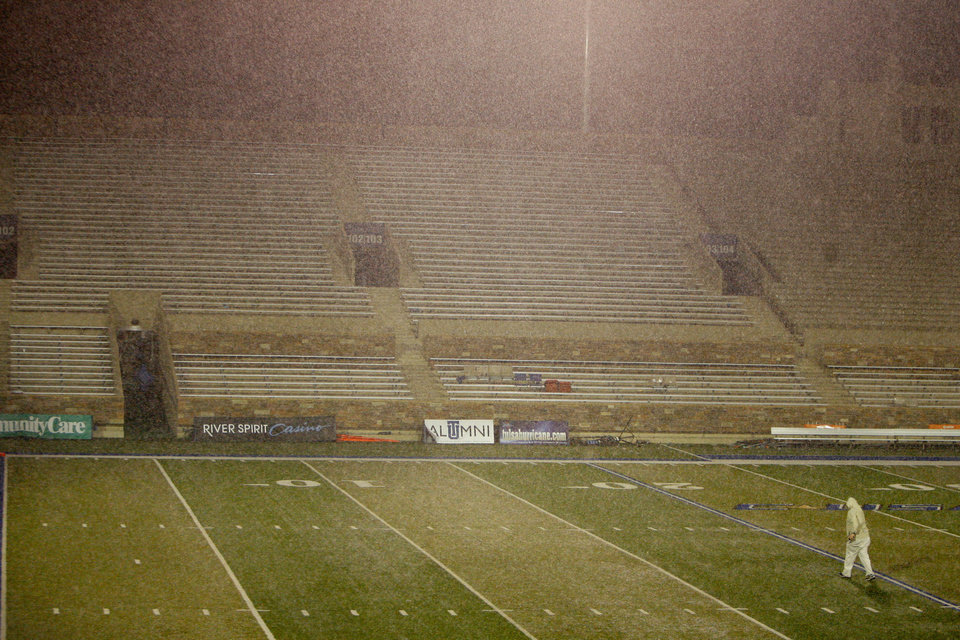 Photo - A person walks across the field during a rain delay before the Oklahoma State-Tulsa game on Saturday. Photo by Sarah Phipps, The Oklahoman