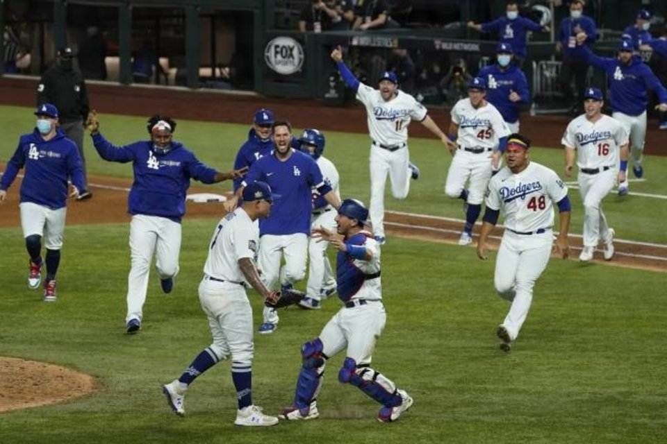 Photo -  The Los Angeles Dodgers race out of their dugout to celebrate their 3-1 win over the Tampa Bay Rays in Game 6 of the World Series on Tuesday in Arlington, Texas. [AP Photo/Tony Gutierrez]