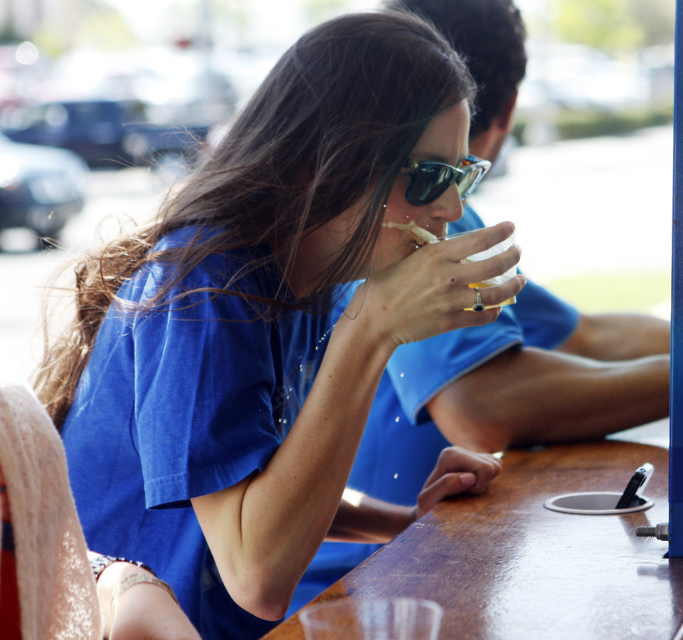 Photo -  Natalie Hodgen spills her beer as the Bricktown Bike Bar hits a bump in the road during a trip around Bricktown in Oklahoma City. Photo by KT King, The Oklahoman    -