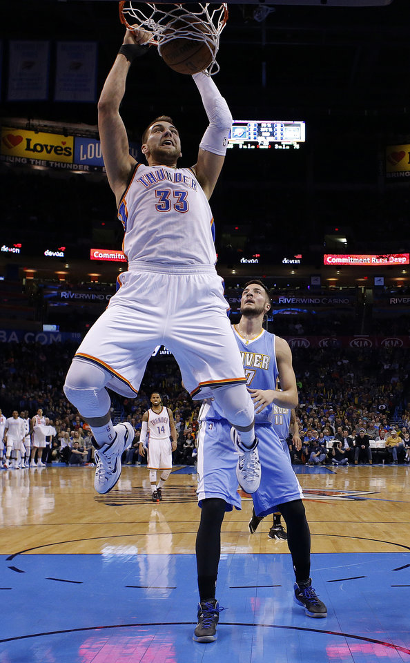 Photo - Oklahoma City's Mitch McGary (33) dunks in front of Denver's Joffrey Lauvergne (77) during the NBA game between the Oklahoma City Thunder and the Denver Nuggets at Chesapeake Energy Arena in Oklahoma City, Sunday, Feb. 22, 2015. Photo by Sarah Phipps, The Oklahoman