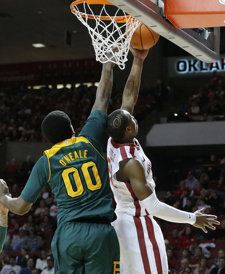 Photo - Oklahoma guard Buddy Hield, right, shoots in front of Baylor forward Royce O'Neale (00) in the second half of an NCAA college basketball game in Norman, Okla., Saturday, Feb. 8, 2014. Oklahoma won 88-72. (AP Photo/Sue Ogrocki)