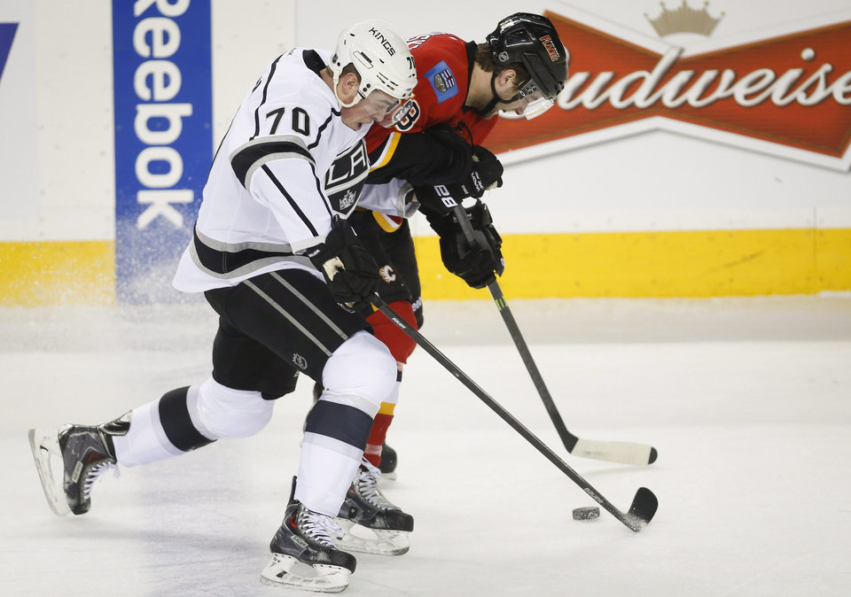 Photo - Los Angeles Kings' Tanner Pearson, left, battles Calgary Flames' Ben Hanowski for the puck during the first period of an NHL hockey game in Calgary, Alberta, Monday, March 10, 2014. (AP Photo/The Canadian Press, Jeff McIntosh)