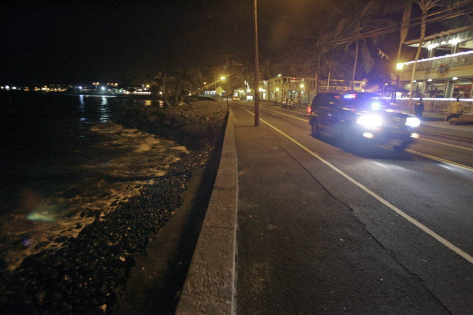 Photo - A police car drives along empty Ali'i Drive in Kailua-Kona, Hawaii, Thursday, March 10, 2011.  A tsunami warning following an earthquake in Japan forced the evacuation of coastal areas of the island. Tsunami waves spawned by a massive earthquake in Japan have hit Hawaii early Friday. The Pacific Tsunami Warning Center says Kauai was the first island hit by the tsunami, which was quickly sweeping through the Hawaiian Island chain. Officials predicted Hawaii would experience waves up to 6 feet.  (AP Photo/Chris Stewart) ORG XMIT: HICS101