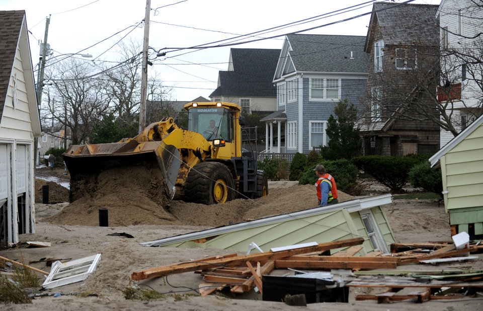 Photo -   A crew works to clear debris in the aftermath of Sandy on Tuesday, Oct. 30, 2012, in Fairfield, Conn. Sandy, the storm that made landfall Monday, caused multiple fatalities, halted mass transit and cut power to more than 6 million homes and businesses. (AP Photo/The Connecticut Post, Autumn Driscoll) MANDATORY CREDIT