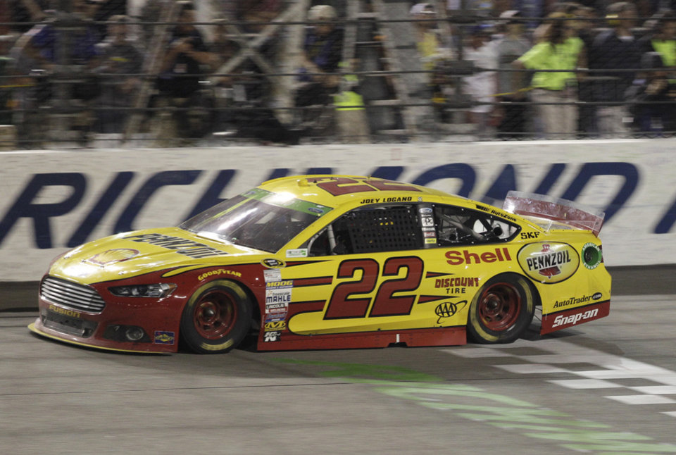 Photo - Joey Logano crosses the finish line to win the NASCAR Sprint Cup auto race at Richmond International Raceway in Richmond, Va., Saturday, April 26, 2014. (AP Photo/Steve Helber)