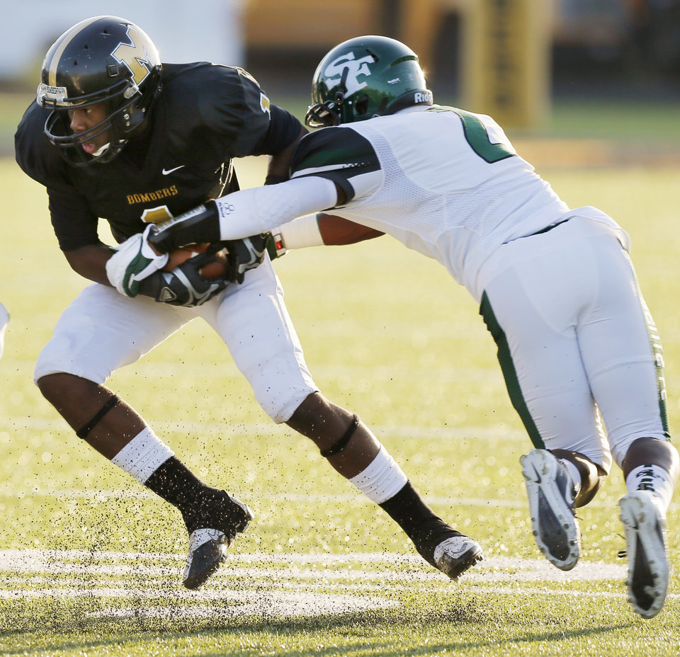 Photo - Edmond Santa Fe's Trevan Smith (2) tries to stop Cedric Fair (1) of Midwest City during the high school football game between Midwest City and Edmond Santa Fe at Rose Field in Midwest City, Okla., Thursday, Aug. 30, 2012. Photo by Nate Billings, The Oklahoman