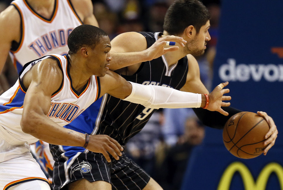 Photo - Oklahoma City's Russell Westbrook (0) tries to steal the ball from Orlando's Nikola Vucevic (9) during an NBA basketball game between the Oklahoma City Thunder and the Orlando Magic at Chesapeake Energy Arena in Oklahoma City, Monday, Feb. 2, 2015. Photo by Nate Billings, The Oklahoman