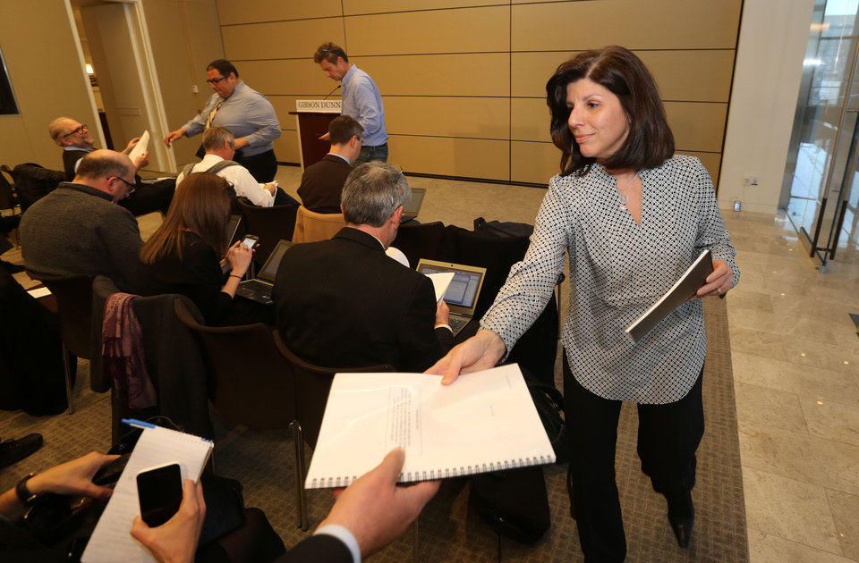 Photo - Phyllis DiGiaimo, an assistant to lawyer Randy Mastro, hands out copies of the executive report before a news conference on Thursday, March 27, 2014 in New York.  The taxpayer-funded report released Thursday concludes the September lane closures near the heavily traveled George Washington Bridge were intended to target a local mayor. But there was no evidence found that it was because the mayor wouldn't endorse New Jersey Gov. Chris Christie. The report finds that former Port Authority of New York and New Jersey official David Wildstein and ex-Christie aide Bridget Kelly were behind the closures. The lawyers also found no evidence that Christie tied Superstorm Sandy aid for Hoboken to support for a private redevelopment project. Federal prosecutors are investigating the lane closings. State lawmakers are also conducting their own probe. (AP Photo/The Star-Ledger, John Munson, Pool)