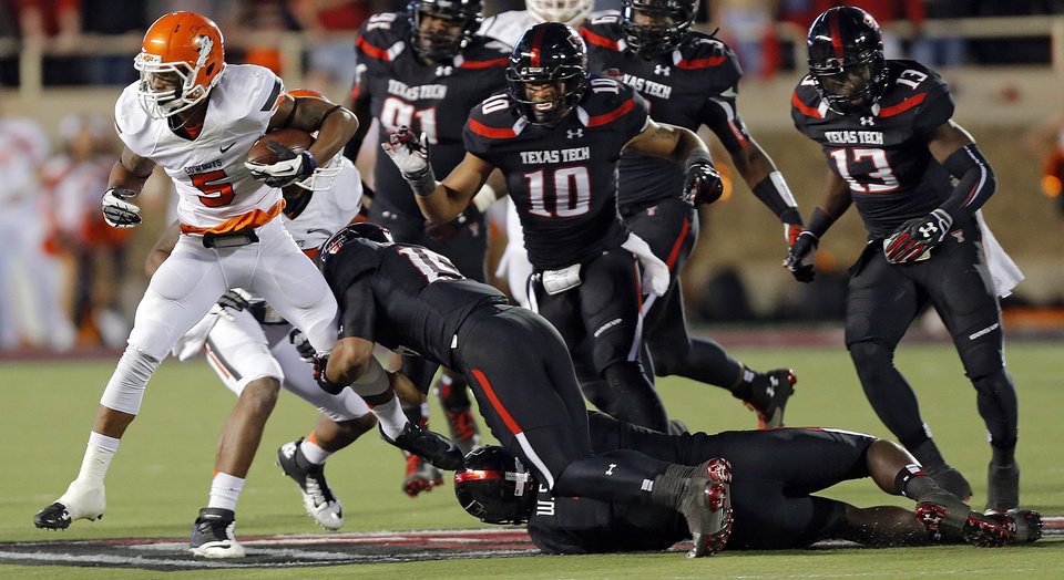Oklahoma State 's Josh Stewart (5) tries to run past the Texas Tech defense during the college football game between the Oklahoma State University Cowboys (OSU) and the Texas Tech University Red Raiders (TTU) at Jones AT&T Stadium in Lubbock, Tex. on Saturday, Nov. 2, 2013.  Photo by Chris Landsberger, The Oklahoman