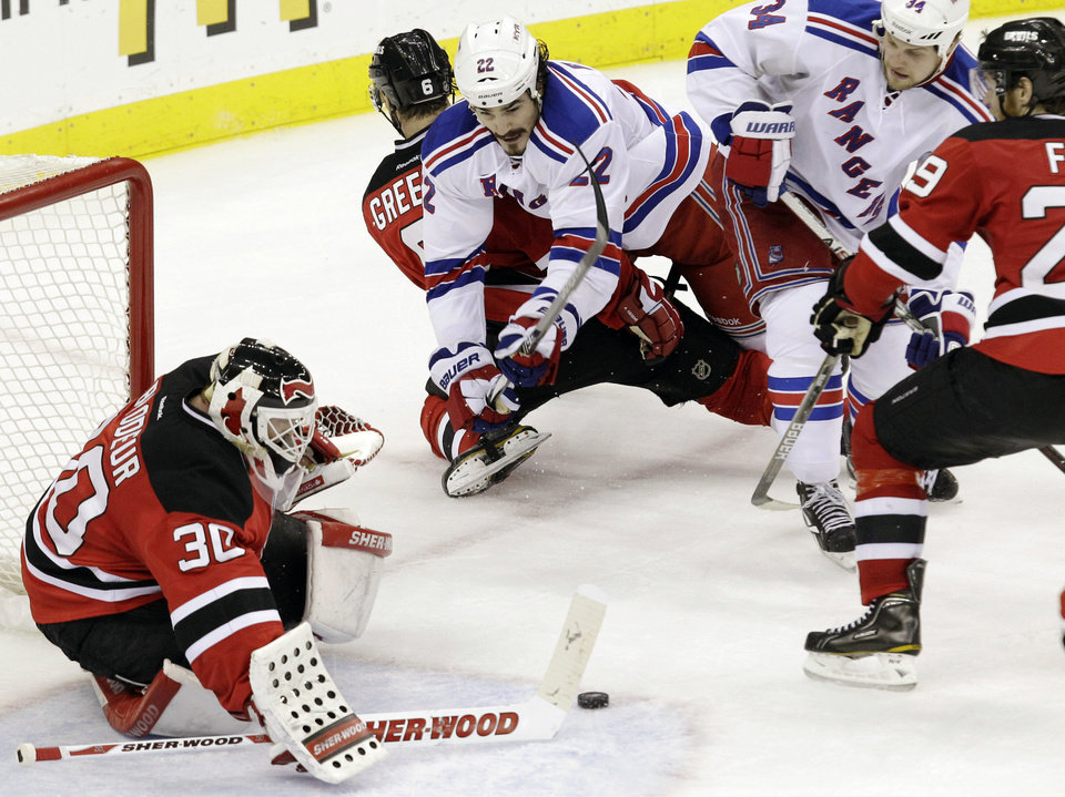 Photo -   New Jersey Devils goalie Martin Brodeur makes a save as defenseman Andy Greene (6) holds back New York Rangers centers Brian Boyle (22) and John Mitchell in the third period during Game 4 of their NHL Eastern Conference Final series, Monday, May 21, 2012, in Newark, N.J. The Devils won 4-1. (AP Photo/Kathy Willens)