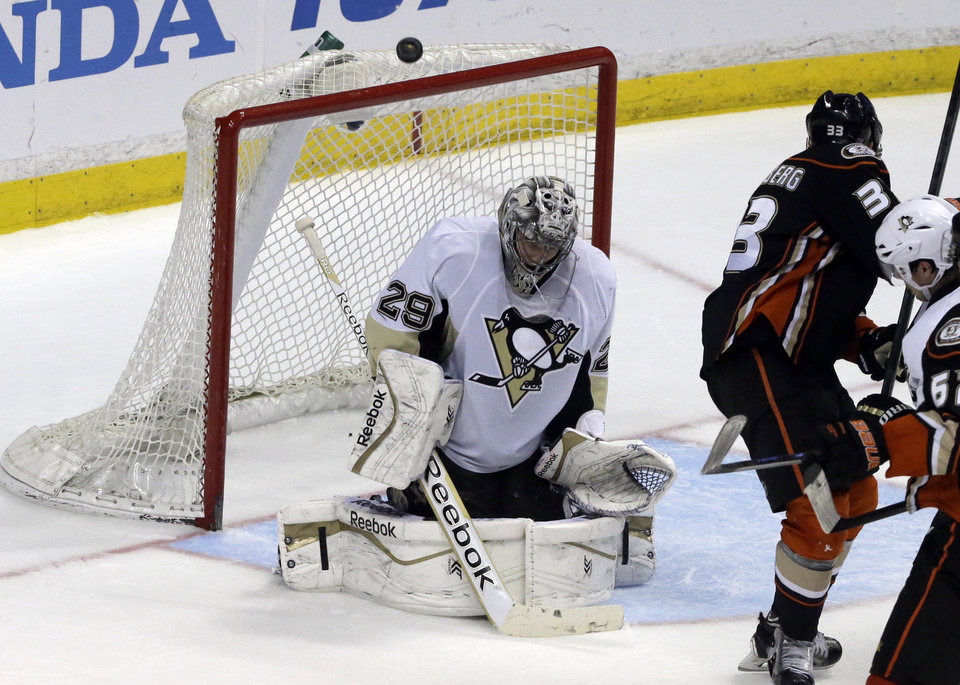 Photo - Pittsburgh Penguins goalie Marc-Andre Fleury (29) blocks the puck with Anaheim Ducks right winger Jakob Silfverberg (33), of Sweden, at right in the second period of an NHL hockey game in Anaheim, Calif., Friday, March 7, 2014.  (AP Photo/Reed Saxon)