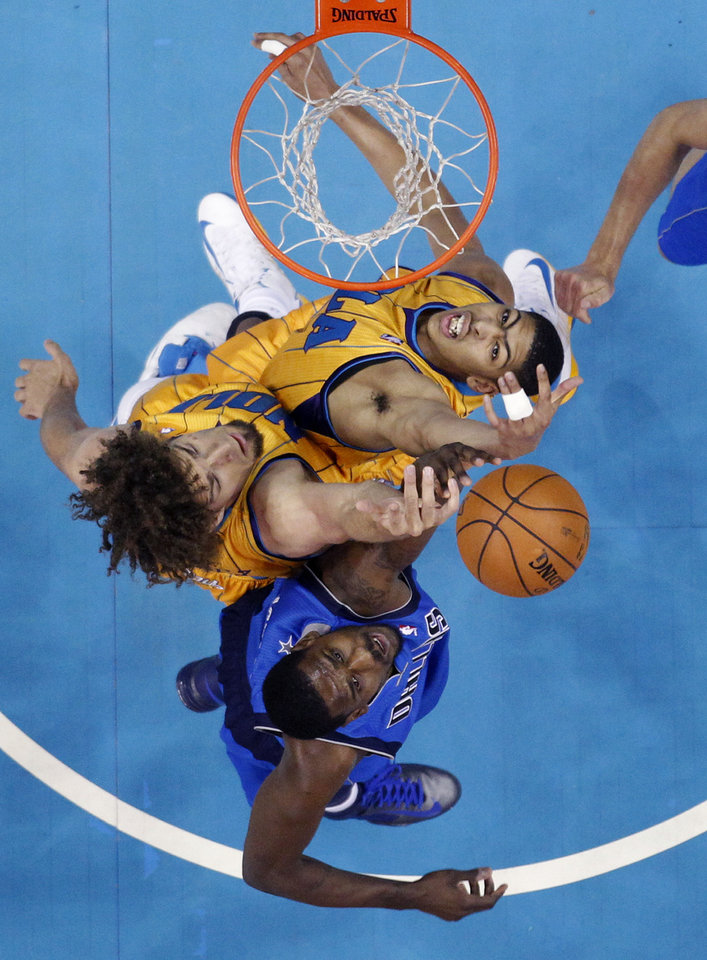 New Orleans Hornets forward Anthony Davis, top and center Robin Lopez battle for the ball under the basket against Dallas Mavericks center Bernard James, bottom, in the first half of an NBA basketball game in New Orleans, Friday, Feb. 22, 2013. (AP Photo/Gerald Herbert)