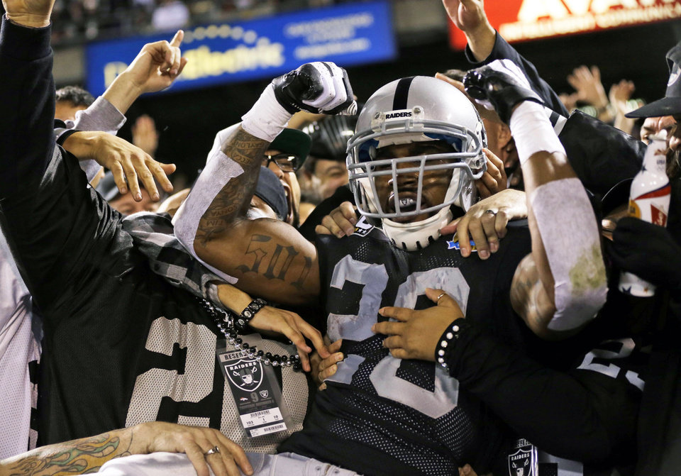 Photo - Oakland Raiders running back Darren McFadden is mobbed by fans after scoring a touchdown on a 6-yard pass during the second quarter of an NFL football game against the Denver Broncos in Oakland, Calif., Thursday, Dec. 6, 2012. (AP Photo/Marcio Jose Sanchez)