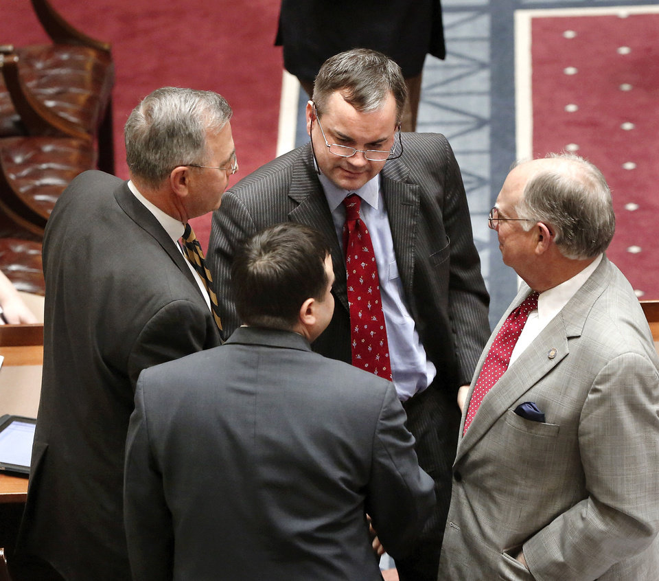 Photo - Senate minority leader Sean Burrage, facing camera, walks over to Senate president pro tempore Brian Bingman, left, and Sen. Anthony Sykes, back to camera, to shake their hands immediately after Burrage and Bingman garnered enough votes to pass  SB 1062  after a contentious debate on the Senate floor. Joining in offering congratulations is Sen. John Ford, right, assistant floor leader.  Oklahoma senators debated a Republican-sponsored workers comp reform bill more than an hour Wednesday afternoon, Feb. 27, 2013,  before passing it by a wide margin, and sending the  legislation to the House for state representatives to consider.   Photo by Jim Beckel, The Oklahoman