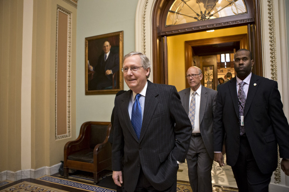 Photo - Senate Minority Leader Mitch McConnell, R-Ky., followed by Sen. Pat Roberts, R-Kan., second from right, leaves the Senate chamber to meet with fellow Republicans  in a closed-door session as the