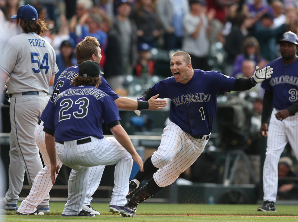 Photo - As Los Angeles Dodgers relief pitcher Chris Perez, far left, heads to the dugout, Colorado Rockies' Brandon Barnes, front right, celebrates driving in the winning run with teammates Corey Dickerson and Charlie Culberson, front left, in the 10th inning of the Rockies' 5-4 victory in 10 innings in a baseball game in Denver on Saturday, June 7, 2014. (AP Photo/David Zalubowski)