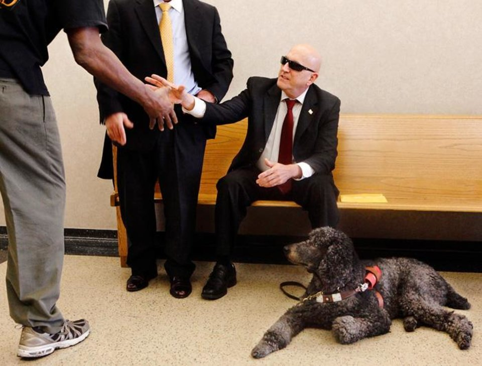 Photo -  TESTIFY / WILLIAM DAVIS: Brent Link, seated, shakes the hand of a person while he and his guide dog, Gipper, wait with Link's son, Stephen, outside a courtroom inside the Cleveland County Courthouse Monday morning, Feb, 8, 2010.  Link testified Monday in the murder trial of William Eugene Davis, 52. Photo by Jim Beckel, The Oklahoman ORG XMIT: KOD