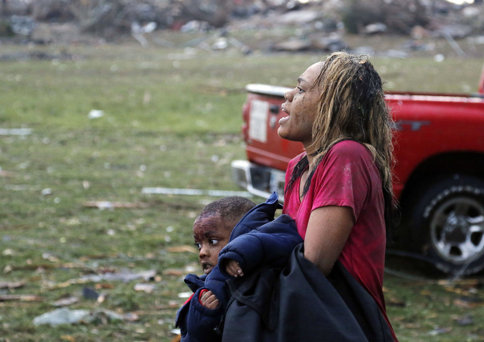 A woman carries an injured child to a triage center near the Plaza Towers Elementary School in Moore, Okla., Monday, May 20, 2013. A tornado as much as a mile (1.6 kilometers) wide with winds up to 200 mph (320 kph) roared through the Oklahoma City suburbs Monday, flattening entire neighborhoods, setting buildings on fire and landing a direct blow on an elementary school.  (AP Photo/Sue Ogrocki) ORG XMIT: OKSO113