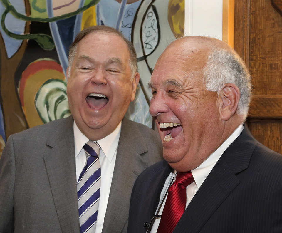 Photo - University of Oklahoma President David Boren, left, and state lawmaker Jerry McPeak, representing McIntosh and Muskogee Counties, laugh after posing for a photo at the end of a ceremony in which the University of Oklahoma transferred ownership of the George Nigh Rehabilitation Center in Okmulgee to the Muscogee (Creek) Nation during a signing ceremony in Boren's office Monday. McPeak is a member of the Creek Nation.  Photo  by Jim Beckel, The Oklahoman.  Jim Beckel