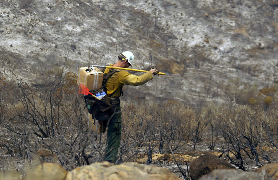 A firefighter carries tools down a burned hill after a wildfire in Point Mugu on Friday, May 3, 2013. A huge wildfire carved a path to the sea and burned on the beach Friday, but firefighters got a break as gusty winds turned into breezes. Temperatures remained high, but humidity levels were expected to soar as cool air moved in from the ocean and the Santa Ana winds retreated. (AP Photo/Nick Ut) ORG XMIT: LA114