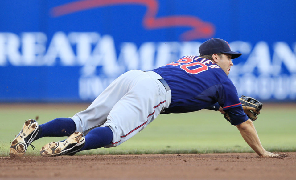 Photo -   Minnesota Twins shortstop Brian Dozier dives for a ground ball hit by Cincinnati Reds' Zack Cozart in the first inning of a baseball game, Friday, June 22, 2012, in Cincinnati. Cozart was given a hit on the play. (AP Photo/Al Behrman)