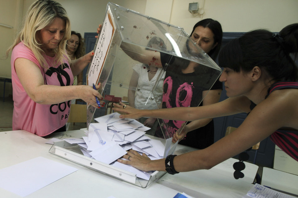 Photo -   Election officials empty a ballot box to count votes during a parliamentary election at a polling station, in Athens, Sunday, June 17, 2012. Greeks are voting Sunday for the second time in six weeks in what is arguably their country's most critical election in 40 years. (AP Photo/Petros Giannakouris)
