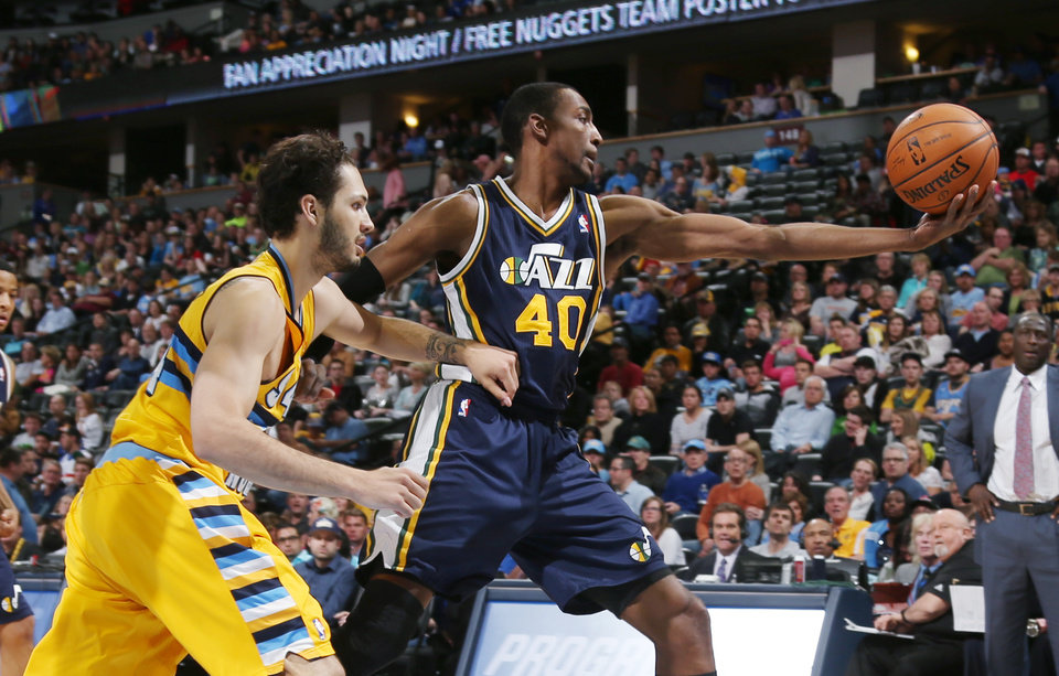 Photo - Utah Jazz forward Jeremy Evans, right, reaches out to pull in a loose ball as Denver Nuggets guard Evan Fournier, of France, covers in the first quarter of an NBA basketball game in Denver on Saturday, April 12, 2014. (AP Photo/David Zalubowski)