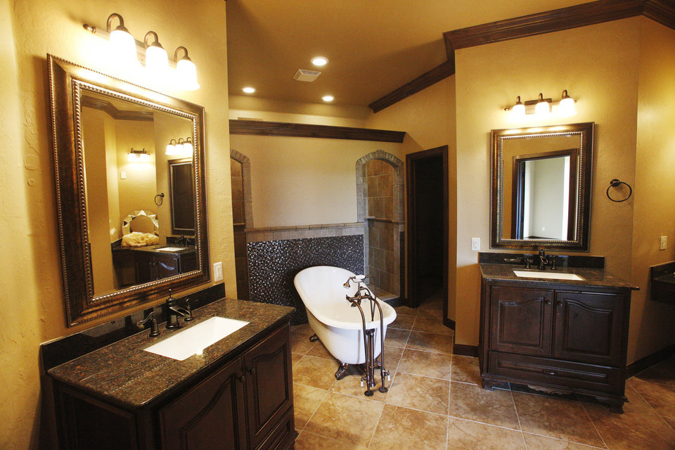 A free-standing tub is flanked by dual walk-in showers and dual vanities in a home by Sun Custom Home at 9032 NW 147 Terrace. Photo by PAUL B. SOUTHERLAND, The Oklahoman