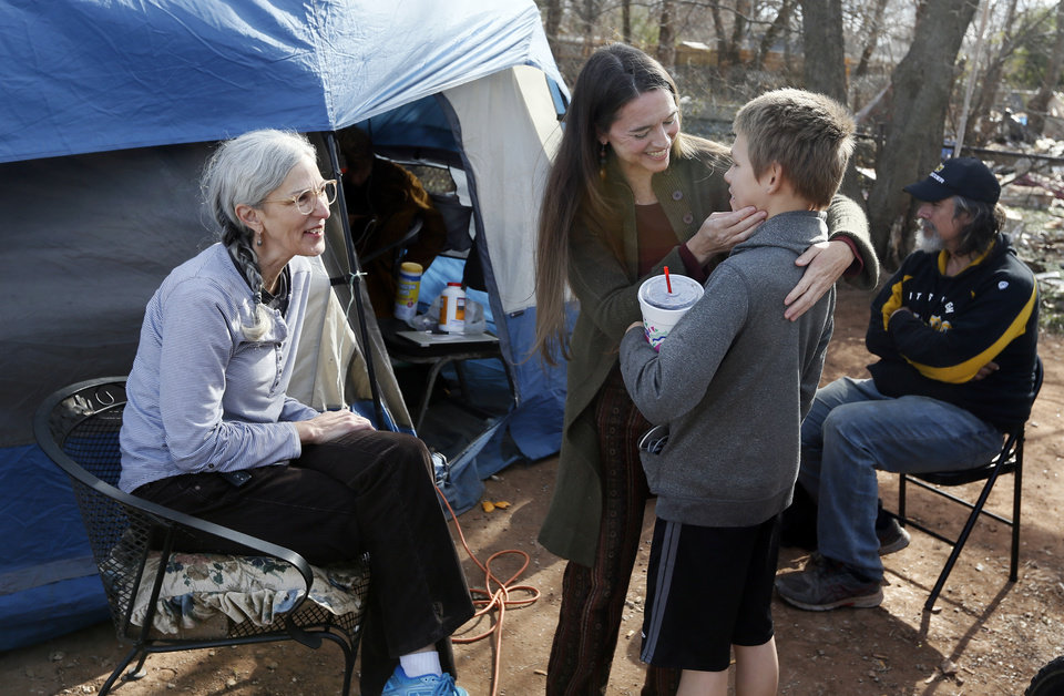 Photo - Jamie Zumwalt, 51, founder and pastor of Joe's Addiction, second from left, talks to Jace Mertes, 13, as volunteer Terry Fife, 66, looks on while people eat a donated lunch out of a tent at 6100 S Cox, near the original location of Joe's Addiction, in Valley Brook, Okla., Monday, Dec. 23, 2019. At right is Clint Higganbotham, 50. While the new site for Joe's Addiction is not ready, Zumwalt and others continue to help the community of people in need who were being served by Joe's Addiction. [Nate Billings/The Oklahoman]