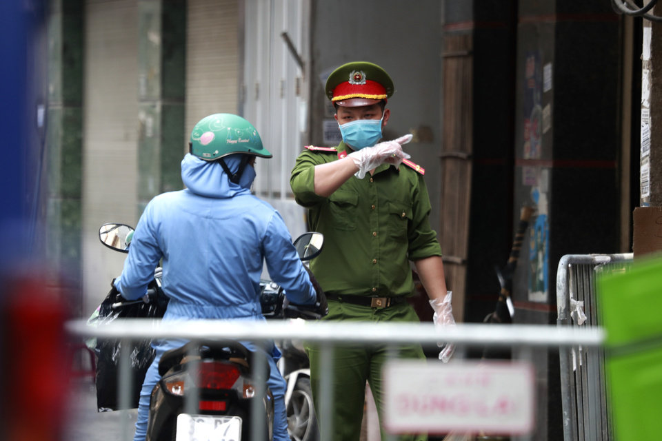 Photo -  A police officer talks to a woman at the barricaded entrance of an alley where one of its residents has COVID-19 in Hanoi, Vietnam on Wednesday, July 29, 2020. Vietnam intensifies protective measures as the number of locally transmissions, starting at a hospital in the popular beach city of Da Nang, keeps increasing since the weekend. (AP Photo/Hau Dinh)