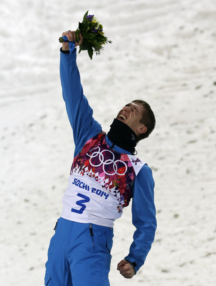 Photo - Anton Kushnir of Belarus celebrates on the podium after winning the gold medal in the men's freestyle skiing aerials at the Rosa Khutor Extreme Park, at the 2014 Winter Olympics, Monday, Feb. 17, 2014, in Krasnaya Polyana, Russia. (AP Photo/Andy Wong)