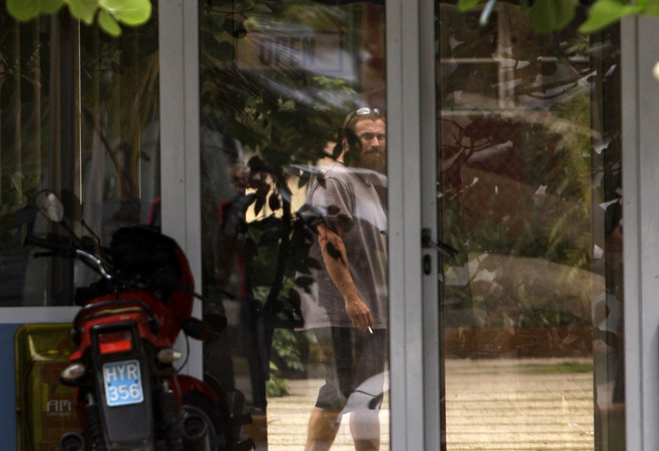Photo - Joshua Michael Hakken stands behind a glass door at the Hemingway Marina in Havana, Cuba, Tuesday, April 9, 2013. Hakken and his wife Sharyn, who had lost custody of their two young boys, allegedly kidnapped them from Sharyn's parents in Florida and fled by boat to Havana. A foreign ministry official told The Associated Press in a written statement Tuesday that Cuba had informed U.S. authorities of the country's decision to turn over Hakken, his wife and their two young boys. She did not say when the handover would occur. (AP Photo/Franklin Reyes)