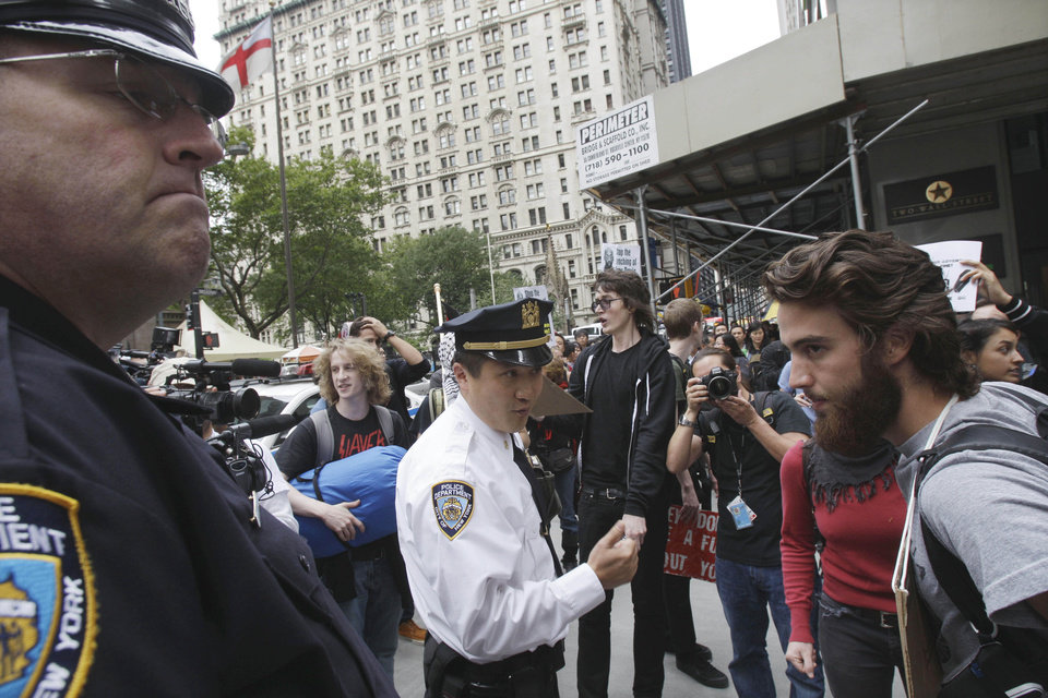 FILE - In this Sept. 17, 2011 file photo, a New York City Police supervisor, center, addresses a member of the crowd as demonstrators affiliated with the Occupy Wall Street movement gather to call for the occupation of Wall Street in New York. Monday, Oct. 17, 2012 marks the one-year anniversary of the Occupy Wall Street movement. (AP Photo/Frank Franklin II, File)