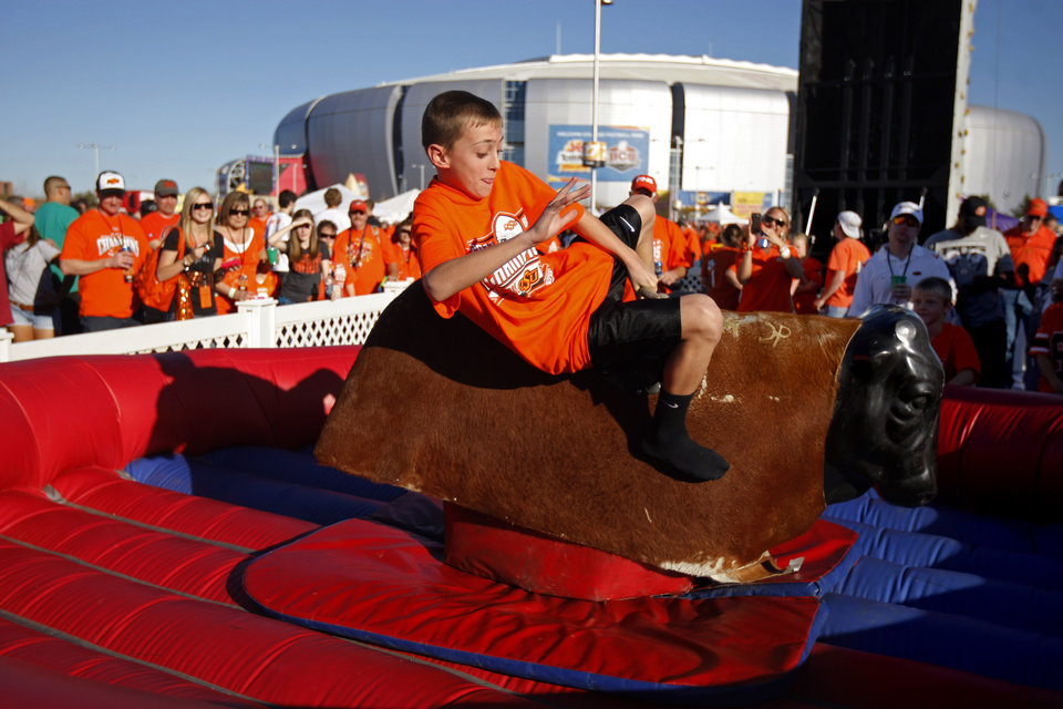 Photo - Logan Rutledge, 12, of Mustang, Okla., rides a mechanical bull before the Fiesta Bowl between the Oklahoma State University Cowboys (OSU) and the Stanford Cardinal at the University of Phoenix Stadium in Glendale, Ariz., Monday, Jan. 2, 2012. Photo by Bryan Terry, The Oklahoman