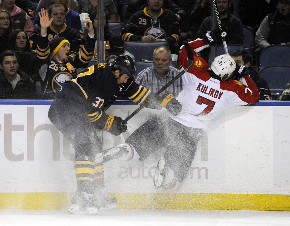 Photo - Buffalo Sabres left winger Matt Ellis (37) knocks Florida Panthers Dmitry Kulikov (7), of Russia, off his skates as they battle for the puck during the first period of an NHL hockey game in Buffalo, N.Y., Thursday, Jan. 9, 2014. (AP Photo/Gary Wiepert)