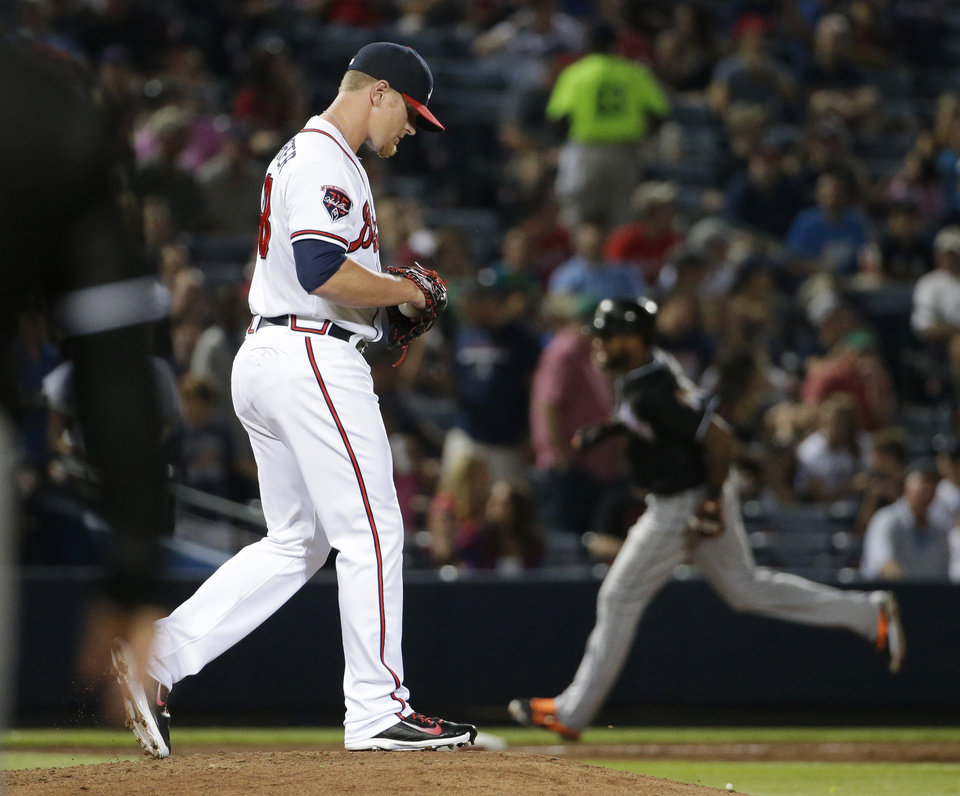 Photo - Atlanta Braves relief pitcher David Carpenter, left, walks on the mound as Miami Marlins' Jordany Valdespin, right, rounds third base after hitting a home run in the seventh inning of a baseball game, Friday, Aug. 29, 2014, in Atlanta. (AP Photo/David Goldman)