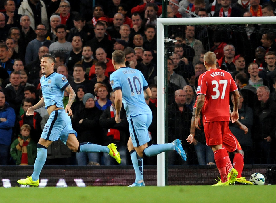 Photo - Manchester City's Stevan Jovetic, left, celebrates after scoring against Liverpool during the English Premier League soccer match between Manchester City and Liverpool at the Etihad Stadium, in Manchester, England, Monday, Aug. 25, 2014. (AP Photo/Rui Vieira)