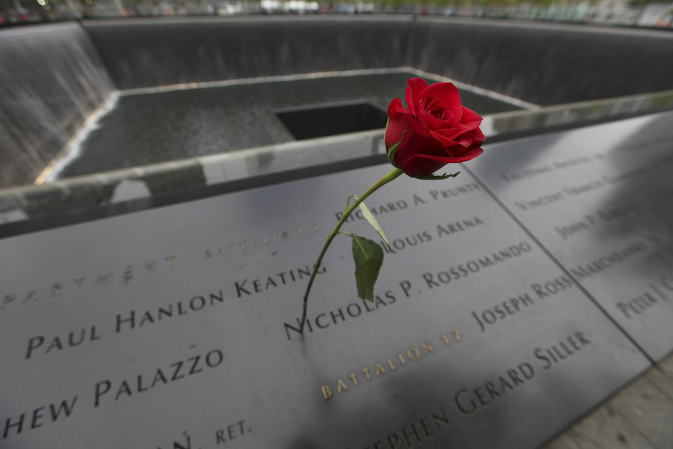 Photo -  A rose is placed on a name engraved along the south reflecting pool at the Ground Zero memorial site during the May 15 dedication ceremony of the National September 11 Memorial Museum in New York. AP Photo   Allan Tannenbaum -