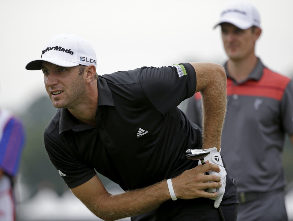 Photo - Dustin Johnson, left, watches his tee shot off the seventh hole as Justin Rose, of England, right, waits his turn during the third round of play in the Tour Championship golf tournament at East Lake Golf Club, in Atlanta, Saturday, Sept. 21, 2013. (AP Photo/David Goldman)
