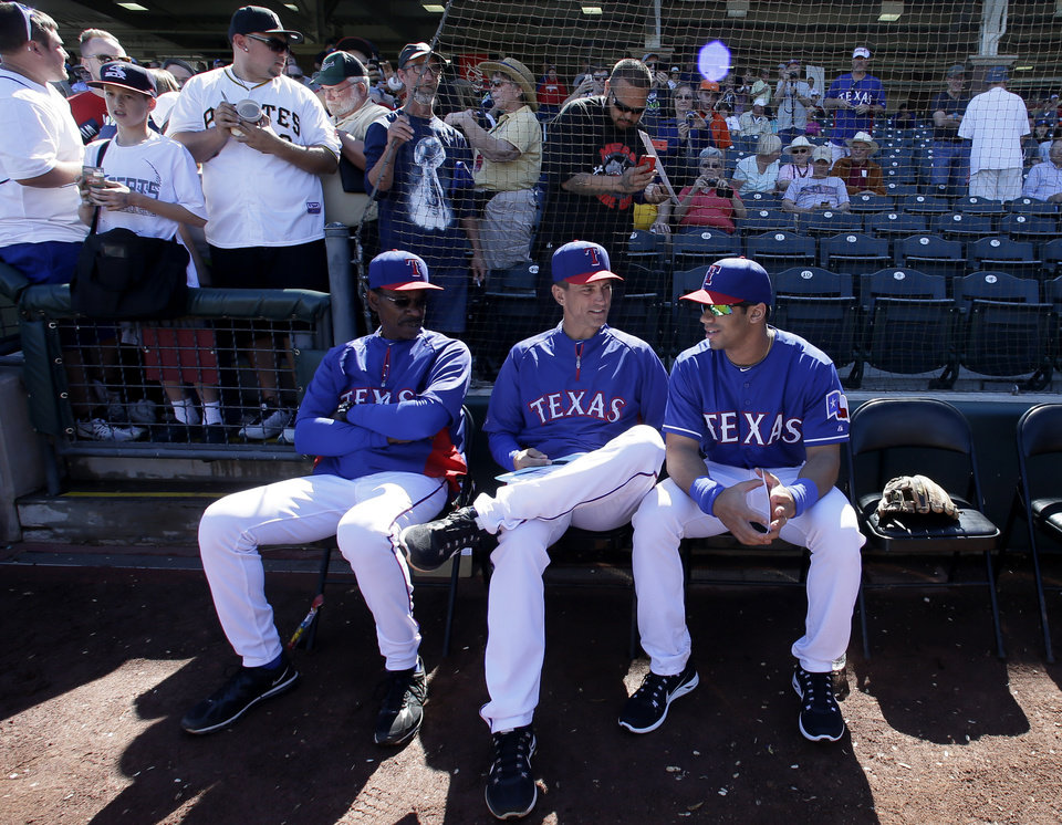 Photo - Texas Rangers' Ron Washington and bench coach Tim Bogar, center, talk with Seattle Seahawks quarterback Russell Wilson, right, before the start of a spring training exhibition baseball game against the Cleveland Indians, Monday, March 3, 2014, in Surprise , Ariz. (AP Photo/Tony Gutierrez)