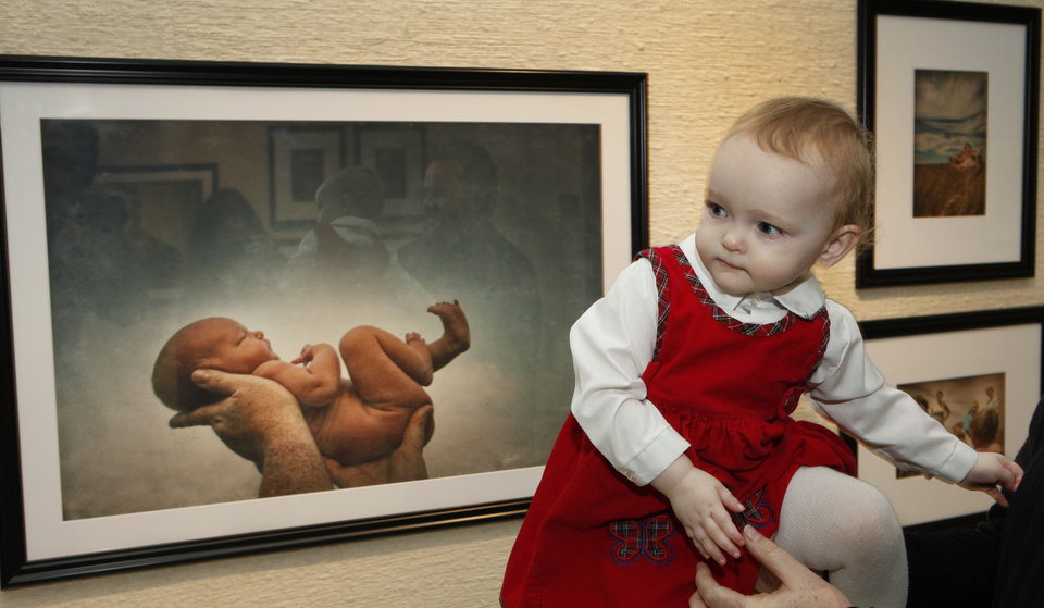 Photo - Brandy McDonnell's 21-month-old daughter Brenna is shown on March 21 with the photograph of her as a newborn taken by M.J. Alexander and exhibited at the Capitol's North Gallery.  Photo By David McDaniel/The Oklahoman  David McDaniel - The Oklahoman
