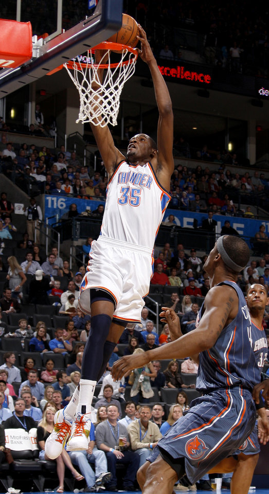 Oklahoma City's Kevin Durant (35) dunks the ball beside Charlotte's Dante Cunningham (44) and Boris Diaw (32) during an NBA basketball game between the Oklahoma City Thunder and the Charlotte Bobcats at the Oklahoma City Arena, Friday, March 18, 2011. Photo by Bryan Terry, The Oklahoman