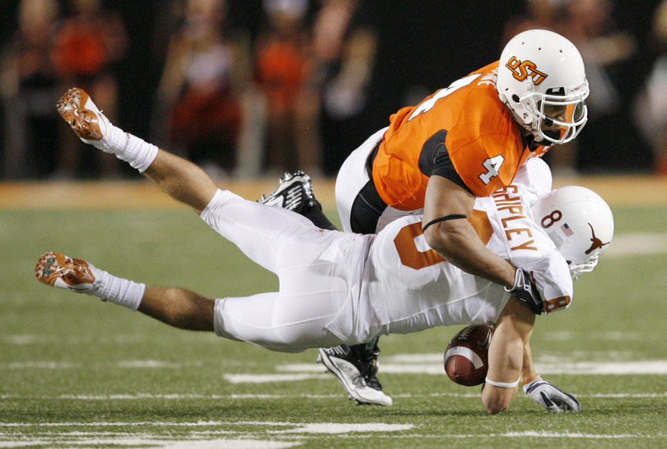 Photo - OSU's Patrick Levine (4) stops Jordan Shipley (8) of Texas after a catch during the college football game between the Oklahoma State University Cowboys (OSU) and the University of Texas Longhorns (UT) at Boone Pickens Stadium in Stillwater, Okla., Saturday, Oct. 31, 2009. Photo by Nate Billings, The Oklahoman
