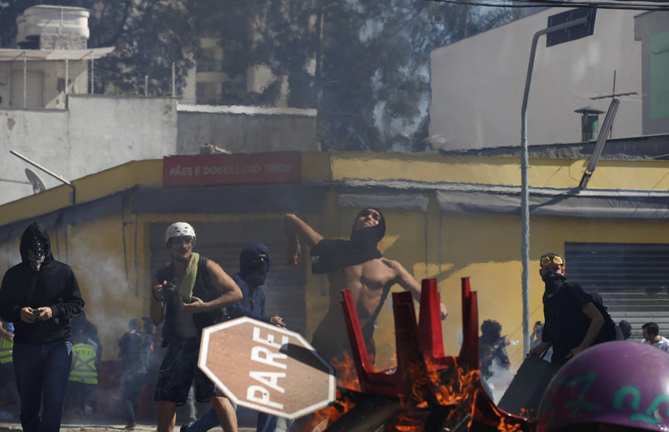 Photo - A protester throws a stone at police from behind a burning barricade during clashes in Sao Paulo, Brazil, Thursday, June 12, 2014. Brazilian police clashed with anti-World Cup protesters trying to block part of the main highway leading to the stadium that hosts the opening match of the tournament. (AP Photo/Dario Lopez-Mills)
