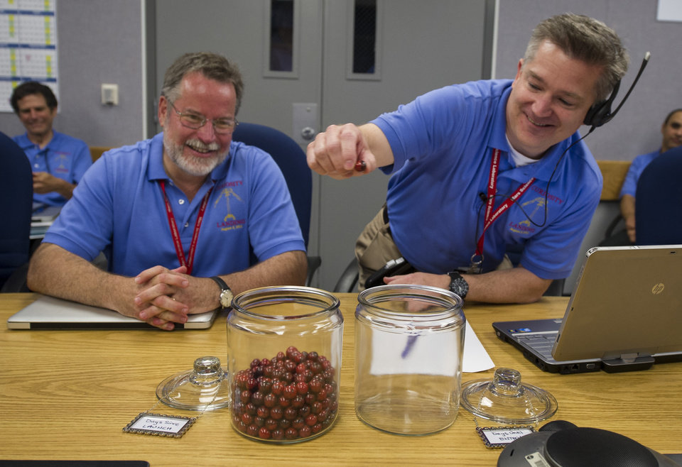 Photo -   In this photo provided by NASA, Mars Science Laboratory (MSL) Flight Systems Chief Engineer Rob Manning, left, smiles as he watches MSL Flight Director Keith Comeaux move the final marble from a jar marked
