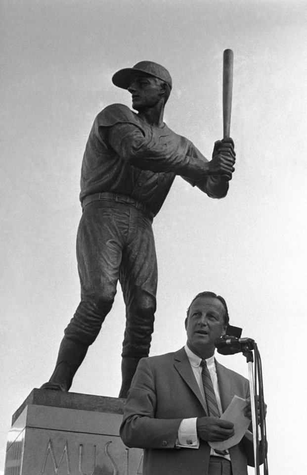 FILE - In this Aug. 4, 1968, file photo, former St. Louis Cardinals baseball player Stan Musial stand near a statue of him at the plate, outside Busch Stadium in St. Louis. Musial, one of baseball's greatest hitters and a Hall of Famer with the Cardinals for more than two decades, has died. He was 92. Stan the Man won seven National League batting titles, was a three-time MVP and helped the Cardinals capture three World Series championships in the 1940s. The Cardinals announced Musial's death in a news release. They said he died Saturday evening, Jan. 19, 2013, at his home surrounded by family. (AP Photo/Fred Waters)