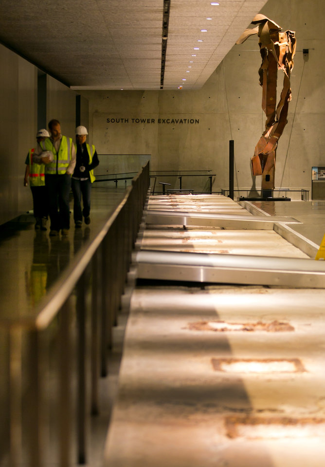 Photo - Workers walk by the World Trade Center south tower excavation display at the National Sept. 11 Memorial Museum, Wednesday, May 14, 2014, in New York. The museum is a monument to how the Sept. 11 terror attacks shaped history, from its heart-wrenching artifacts to the underground space that houses them amid the remnants of the fallen twin towers' foundations. It also reflects the complexity of crafting a public understanding of the terrorist attacks and reconceiving ground zero.  (AP Photo)