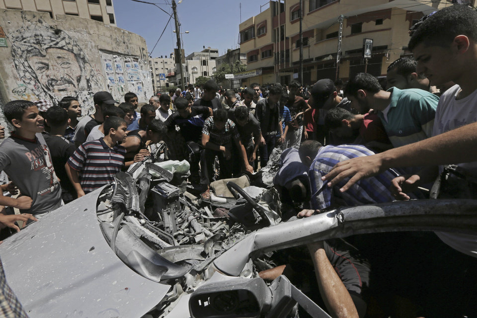 Photo - Palestinians inspect the wreckage of a vehicle following an Israeli airstrike at the main street in Gaza City in the northern Gaza Strip, Thursday, Aug. 21, 2014. At least two were killed in the car outside a grocery shop, and a few others were wounded by the Israel airstrike on a Gaza City street, according to the Palestine Red Crescent Society. (AP Photo/Adel Hana)