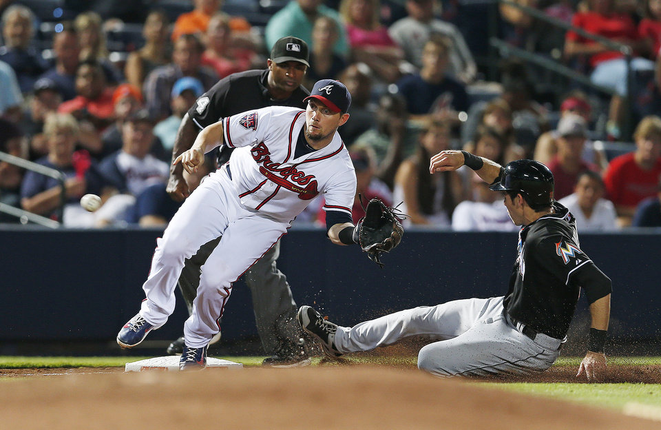 Photo - Miami Marlins' Christian Yelich (21) steals third base as Atlanta Braves third baseman Chris Johnson (23) handles the late throw in the eighth inning of baseball game in Atlanta, Wednesday, July 23, 2014. (AP Photo)